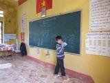 Am 2. Tag haben wir noch Einblick in eine Dorfschule. Unter der Nationalflagge wacht Onkel Ho (chi minh) ueber die Schueler